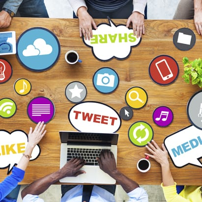 Social media strategy is shown as varied icons at a business table